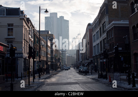 A view down Curtain Road in the Shoreditch Triangle, towards The City. Steam is rising from the financial district. - Stock Photo