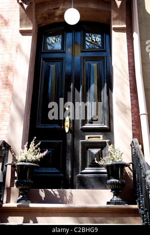 The black front door of a brownstone building in West Village New York Manhattan - Stock Photo