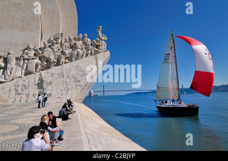 Portugal, Lisbon: Sailing boat on river Tagus passing the Discoveries Monument in Belém - Stock Photo