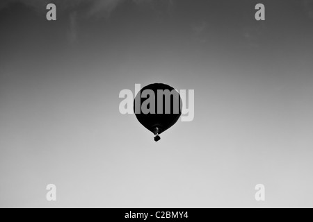 Hot Air balloon silhouetted in a Shropshire evening sky - Stock Photo