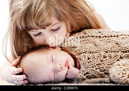 girl kisses her little baby brother - Stock Photo