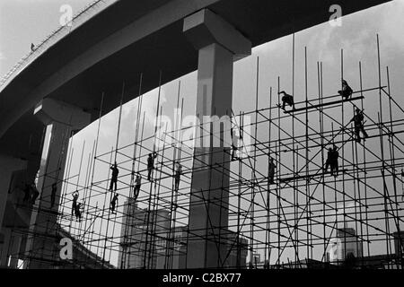Workers on bamboo scaffolding in Shanghai, China. - Stock Photo