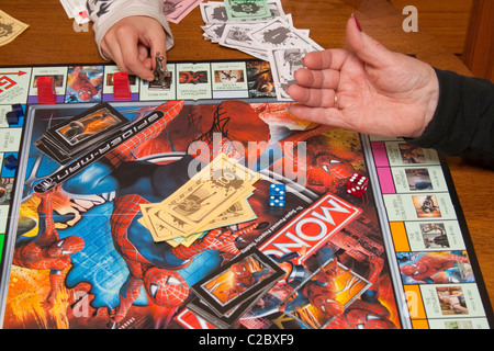 Tossing dice Spiderman Monopoly board game in progress.  St Paul Minnesota MN USA - Stock Photo