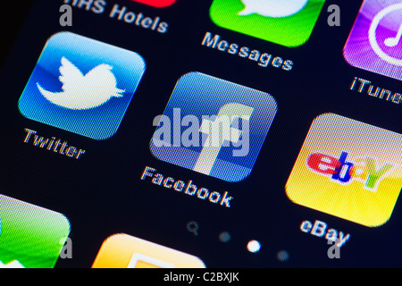 Detail macro image of the iphone touch screen. Display shows apps from facebook, twitter, ebay, itunes and messages - Stock Photo