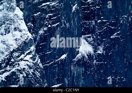 A rugged sheer black mountain cliff face covered in snow and ice. - Stock Photo