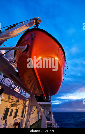 A bright orange emergency rescue lifeboat on a ship in Antarctica. - Stock Photo