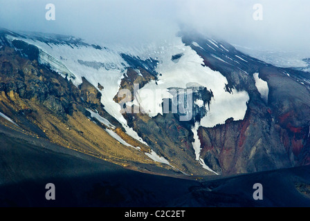 Rugged snow and ice encrusted mountain surrounding a volcanic caldera. - Stock Photo