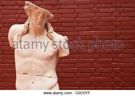 A statue stands against a red brick wall in the Ephesus Museum. - Stock Photo
