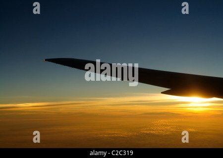 Sunset under airplane wing skyline - Stock Photo