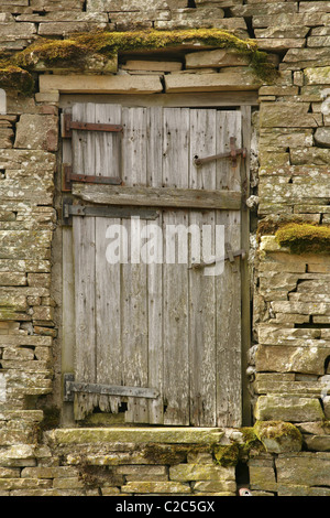 Wooden door in side of old derelict stone barn. - Stock Photo