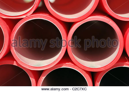 Red plastic pipes stacked. Industrial concept - Stock Photo