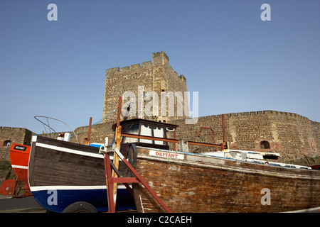 old fishing boats in front of carrickfergus castle in northern ireland - Stock Photo