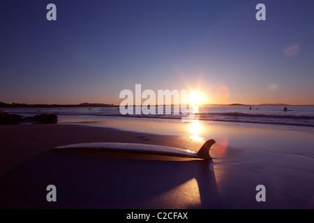 Surfboard on beach at sunset - Stock Photo