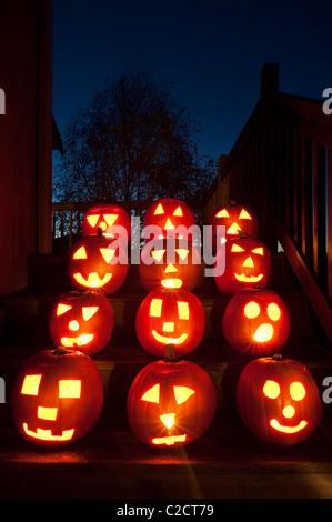 Lit Pumpkins on house steps on Halloween - Stock Photo