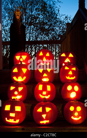 Scary lit carved pumpkins at twilight on stairs with Demon with horns in background on Halloween - Stock Photo
