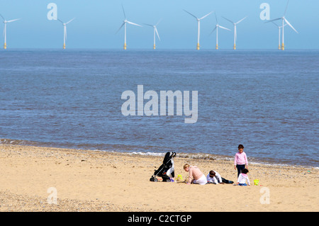 Great Yarmouth, Norfolk. A family sitting on the Beach with Off Shore Wind Turbines on Scrooby Sands, Great Yarmouth - Stock Photo