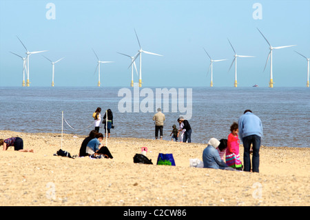 Great Yarmouth, Norfolk. A families sitting on the Beach with Off Shore Wind Turbines on Scrooby Sands, Great Yarmouth - Stock Photo