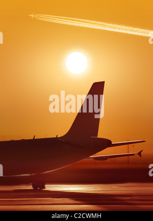 big passenger airplane is waiting for departure in airport, sunset - Stock Photo
