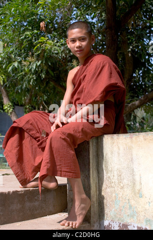 A young Buddhist monk is relaxing at a beautiful temple in Tachilek, Burma (Myanmar). - Stock Photo