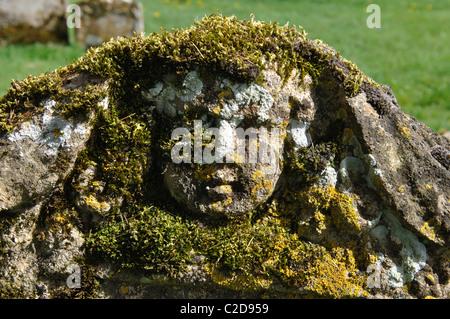 Mossy cherub on gravestone in St. Bartholomew`s churchyard, Winstone, Gloucestershire, England, UK - Stock Photo