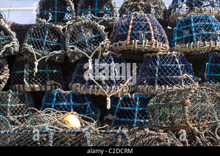 Lobster cages stacked up on a queyside - Stock Photo