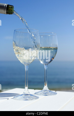 Pouring wine by the sea - Stock Photo