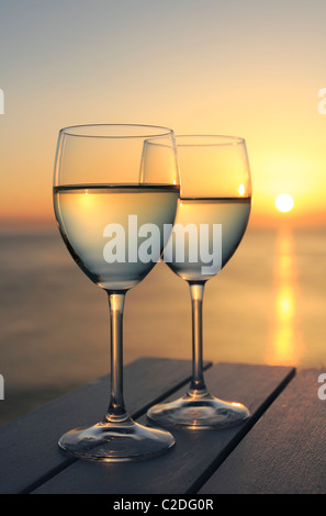 Two glasses of wine by the ocean - Stock Photo