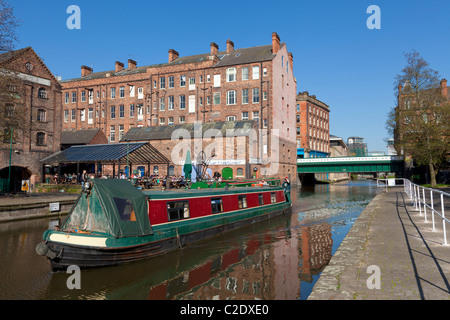 Barge or Narrow boat on the Nottingham canal passing converted warehouses in the city centre Nottingham England - Stock Photo