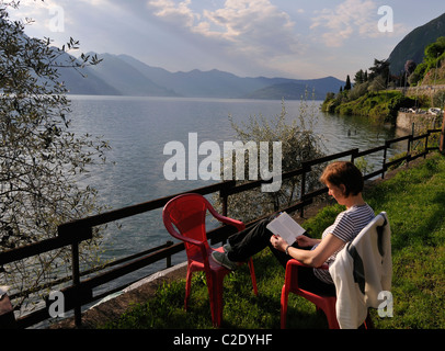 Woman sitting and reading at Lago d Iseo in Riva di Solto, Bergamo, Italy - Stock Photo