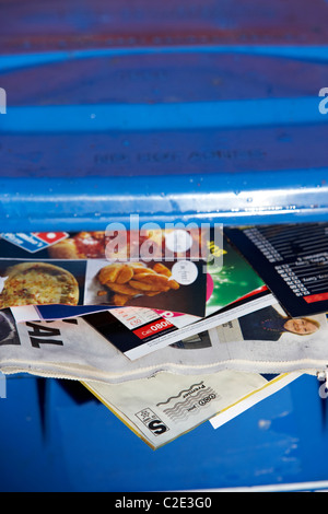 blue paper recycling bin with junk mail and local newspapers sticking out of it and lid not closed in the uk - Stock Photo