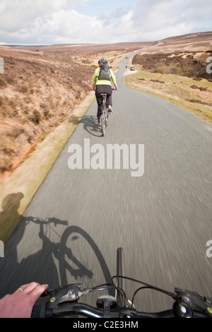 A Woman Mountain Biking Over The North York Moors Road From Stock