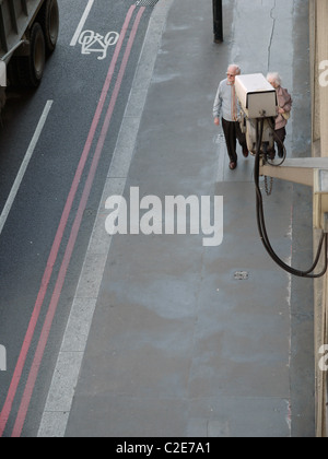 CCTV Surveillance camera mounted on building, with elderly couple walking past - Stock Photo