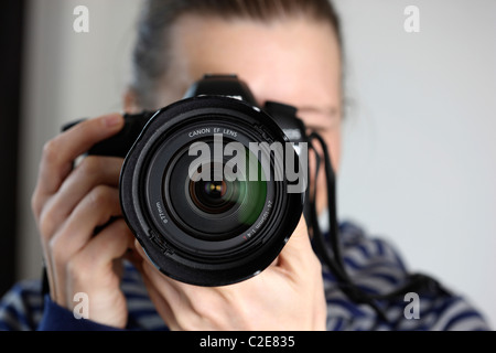 Person, female, looks through the viewfinder of a digital single lens reflex camera. - Stock Photo