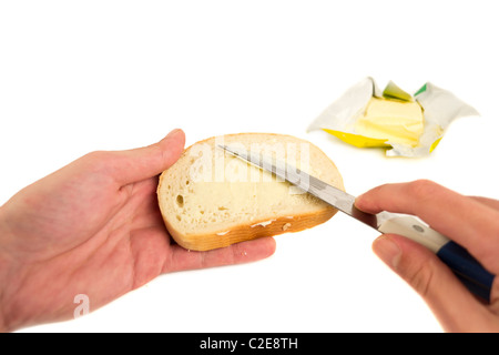 Hand spreading butter on slice of bread,isolated on white - Stock Photo