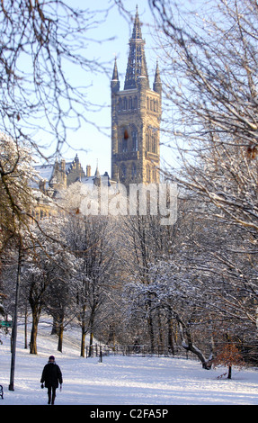 A person walks through Kelvingrove park in Glasgow after a heavy snowfall. The University of Glasgow is pictured - Stock Photo
