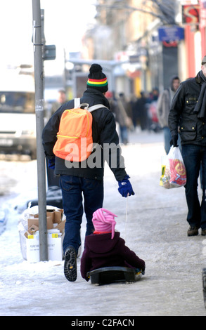 A man drags his child through the streets of Glasgow, Scotland during the coldest winter in decades. - Stock Photo