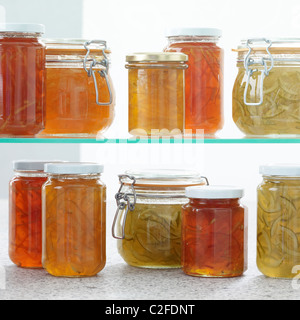 Home made marmalade jars on glass shelf - Stock Photo