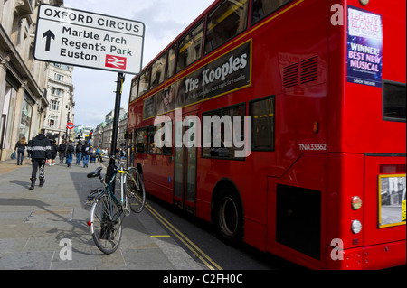 Bus stops next to a bicycle chained to a London street sign post - Stock Photo