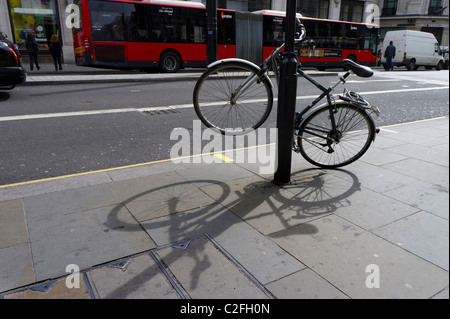 Bicycle chained to a London street post - Stock Photo