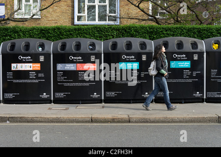 Young woman walking by a row of recycle bins, London, England, UK - Stock Photo