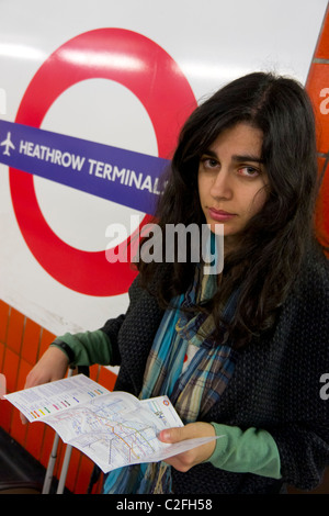 Woman with tube map in hand looking lost at London Heathrow Terminals 1, 2, 3 Underground station - Stock Photo