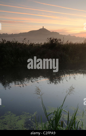 A misty sunrise on the banks of the River Brue in Somerset. Glastonbury Tor is visible in the background through - Stock Photo