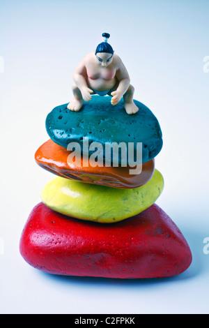 Toy Sumo wrestler on colored stones - Stock Photo