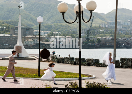 Members Of A Wedding Party And The Bride Walk Along Waterfront In Kholmsk Sakhalin