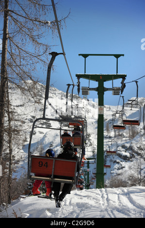 Skiers on a chairlift at the Vogel Ski Centre from the base of the Sija - Zadnji Vogel piste in the Triglav National - Stock Photo
