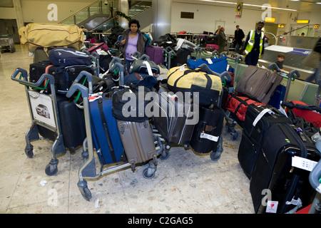 Backlog / back log / backlogged / delayed / piled up / stack / stacked luggage at London Heathrow LHR International - Stock Photo