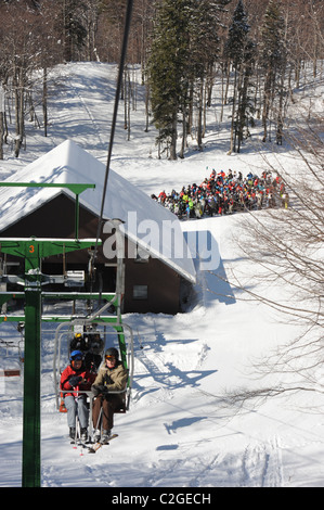 Skiers queue for a chairlift at the Vogel Ski Centre on the the Sija - Zadnji Vogel piste in the Triglav National - Stock Photo