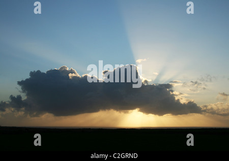 Sun behind a cloud, just before sunset - Stock Photo