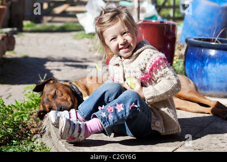 little girl playing with her dog friend - Stock Photo
