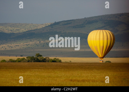 Hot air balloon landing in the Masai Mara, Kenya. - Stock Photo